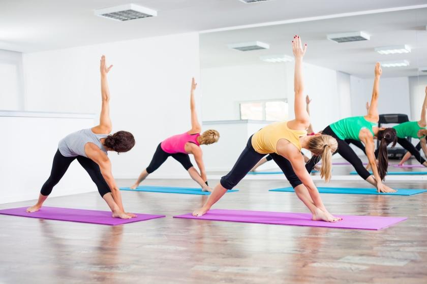 Four girls practicing yoga, Trikonasana / Bikram triangle right
